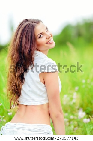 Portrait of a cheerful smiling young woman in a field