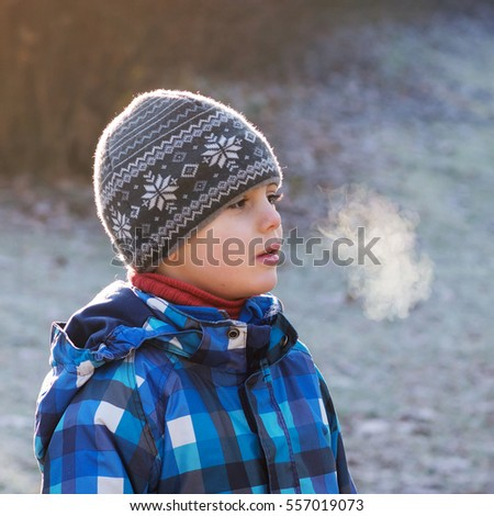 Portrait of a child boy,with vapor coming from his mouth, in a park on  a cold frosty day, weather concept.