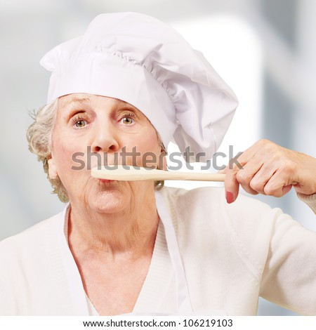 portrait of a cook senior woman with a wooden spoon on a mouth indoor
