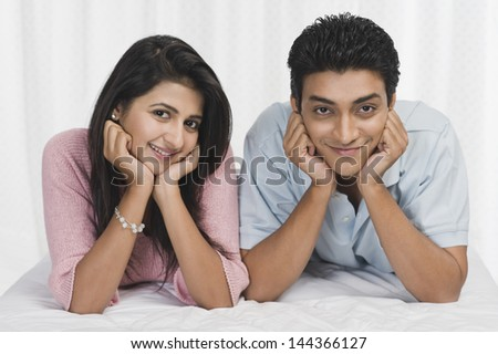 Portrait of a couple lying on the bed and smiling