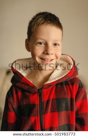 portrait of a cute boy in a red plaid jacket with a hood