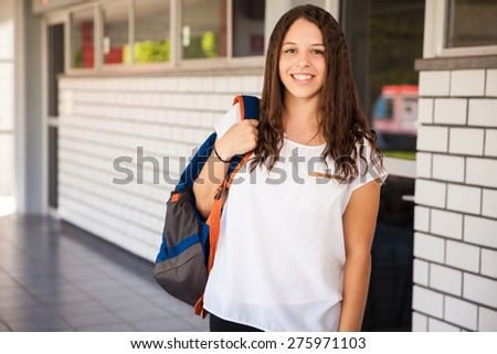 Portrait of a cute brunette carrying a school bag and smiling in a school hallway