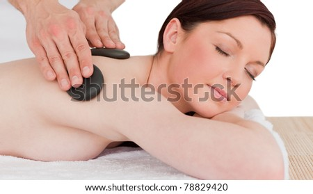 Portrait of a cute red-haired female posing while receiving a massage in a spa