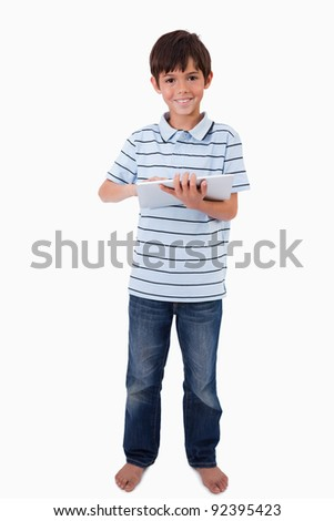 Portrait of a cute smiling boy using a tablet computer against a white background