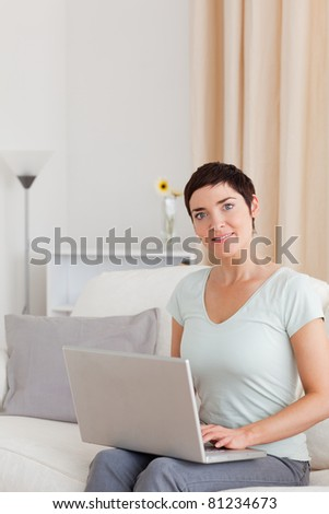 Portrait of a cute woman working with a laptop in her living room