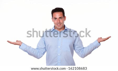 Portrait of a fashionable young man on blue shirt holding out his hands while standing and looking at you on isolated background - copyspace