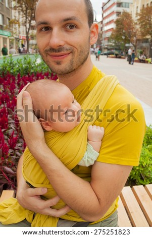 Portrait of a father with his baby in a sling carrier in the street