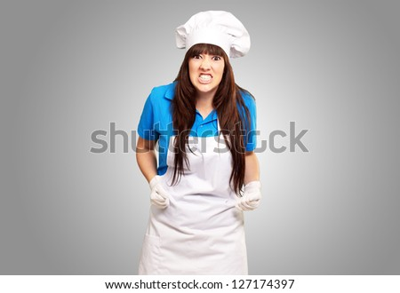 portrait of a female chef clenching on gray background