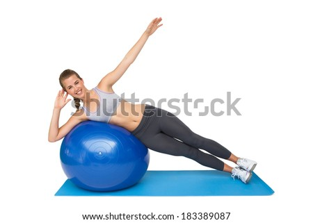 Portrait of a fit young woman stretching on fitness ball over white background