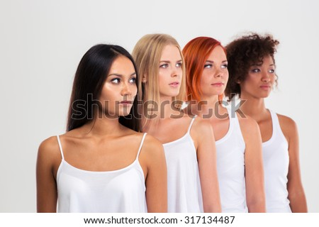 Portrait of a four women standing in a raw and looking away isolated on a white background