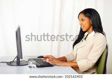 Portrait of a friendly businesswoman working on computer