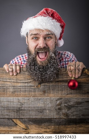 Portrait of a funny bearded man with santa cap holding a red decoration ball over gray background