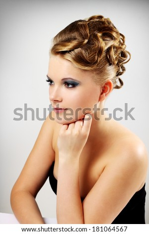 Portrait of a girl with beautiful hairstyle on a gray background