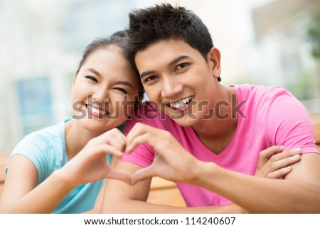 Portrait of a guy and a girl forming a heart shape with their hands