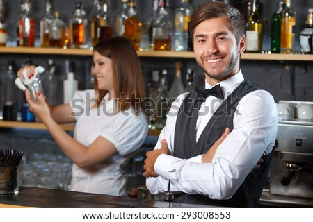 Portrait of a handsome bartender standing at the counter smiling and looking at the camera while a pretty waitress holding a glass and wiping it, shelves full of bottles with alcohol on the background