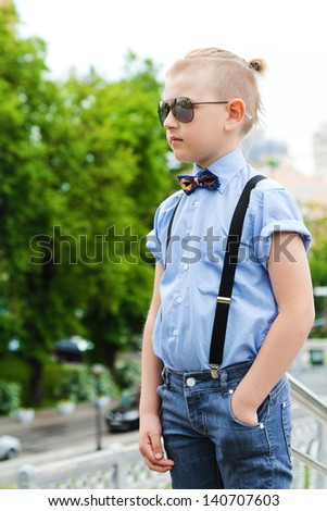 Portrait of a handsome boy with a creative hairstyle on background of the city. A boy with a fashionable hairstyle in blue shirt. Boy in sun goggles. Sunglasses have a little boy. Sad boy.