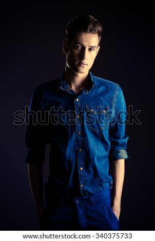 Portrait of a handsome young man in jeans shirt posing over dark background. Men's beauty, fashion. Studio shot.