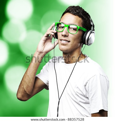 portrait of a handsome young man listening to music over abstract background
