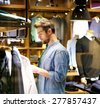 Portrait of a handsome young man shopping for clothes at shop - stock photo