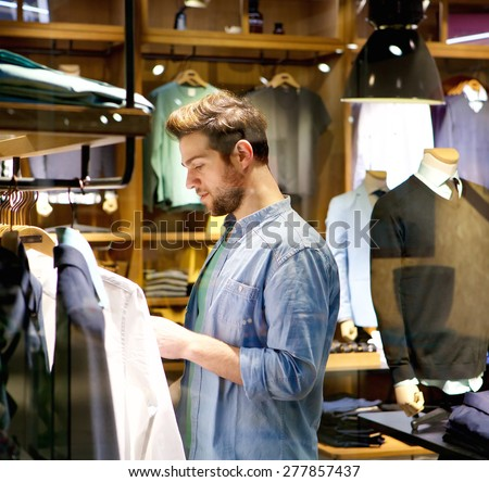 Portrait of a handsome young man shopping for clothes at shop