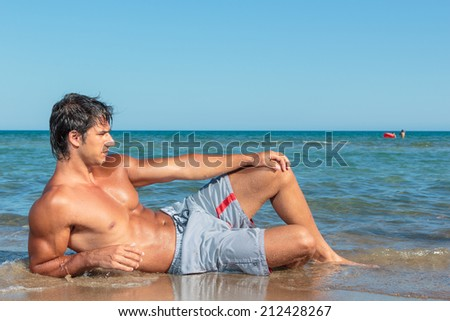 Portrait of a handsome young muscular man in swimwear on the beach