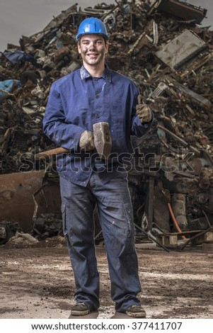 portrait of a handsome young worker at junkyard