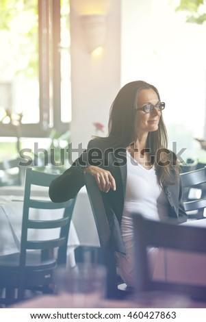 Portrait of a happy and pretty young woman sitting in a restaurant - perhaps she is the owner and just enjoys her break from work.