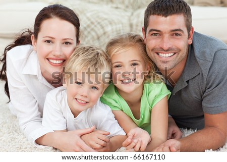 Portrait of a happy family lying on the floor at home