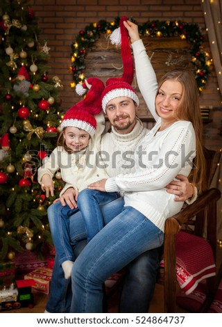 Portrait of a happy family of three man in red Christmas hat. Christmas tree at home in the living room, decorated with festive lights and candles.