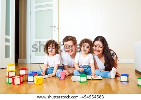 Portrait Of A Happy Family On The Floor, Playing With Cubes. Mother, Father
