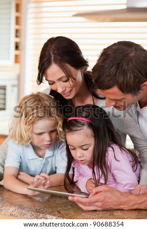 Portrait of a happy family using a tablet computer together in a kitchen