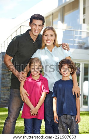Portrait of a happy family with two children in front of a house