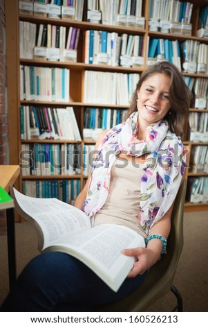 Portrait of a happy female student sitting on chair and with a book in the library