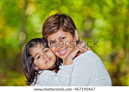 Portrait of a happy Hispanic mother and daughter at the park