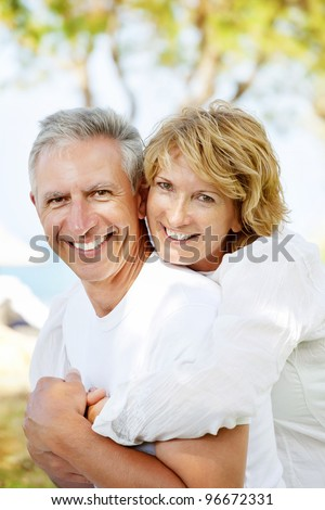 Portrait of a happy mature couple outdoors. Shallow DoF with focus on woman.