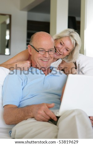 Portrait of a happy senior couple in front of a laptop computer