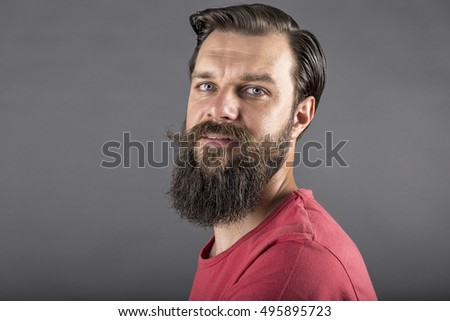 Portrait of a happy stylish man with beard and mustache over gray background