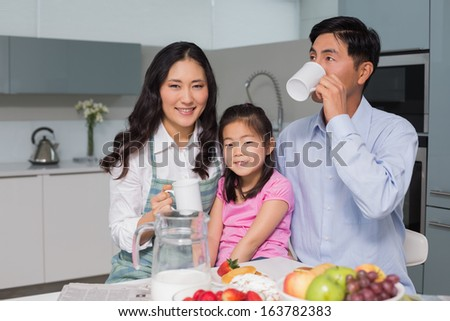 Portrait of a happy young girl enjoying breakfast with parents at table in the house