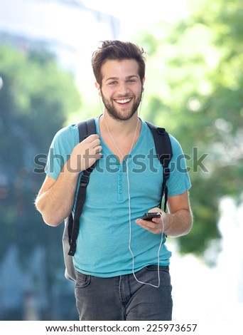 Portrait of a happy young man walking outdoors with cellphone