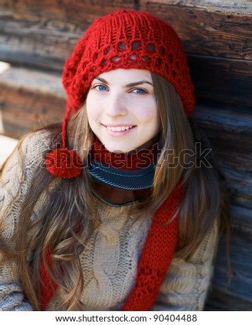 Portrait of a happy young woman against wooden wall with ski mask and red hat.