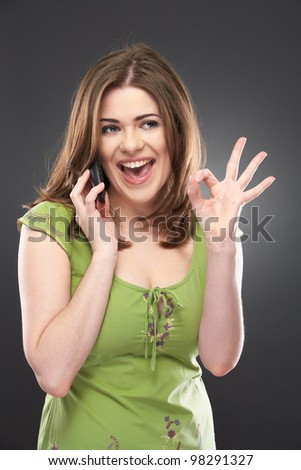 Portrait of a happy young woman doing okay sign and cell phone talking