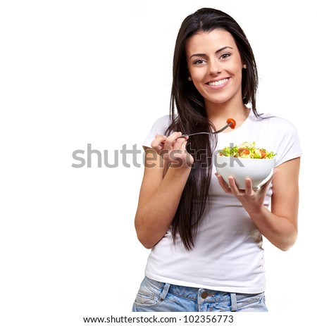 portrait of a healthy woman eating a salad against a white background