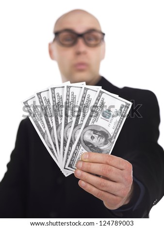 Portrait of a human hand holding a fan of dollar bills with a blurred face of the man on the background