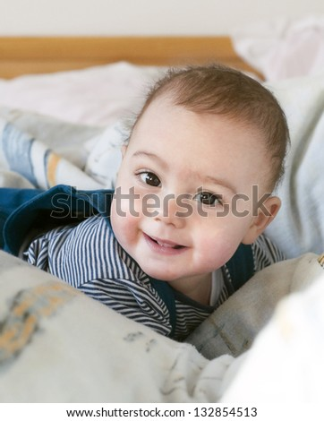 Portrait of a little baby boy lying on his belly in sheets in a bed with a cheeky smile on his face.