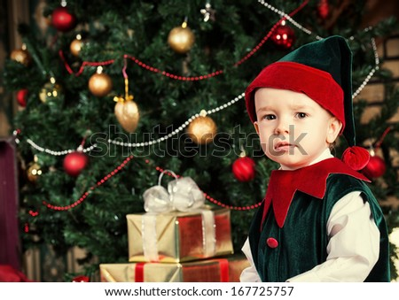 Portrait of a little boy dressed as an elf at home near the Christmas tree.