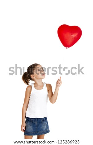 Portrait of a little girl holding and looking to a red balloon, isolated on white background