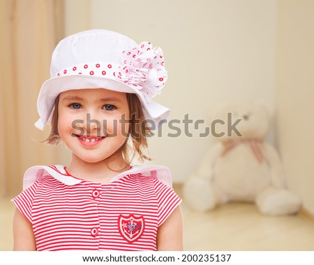 portrait of a little girl in a white cap on a background of a child's room