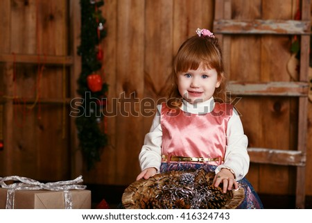 Portrait of a lovely little girl. Portrait of cute little girl among Christmas decorations