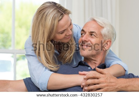 Portrait of a loving mature senior woman embracing man from behind at home. Happy senior couple relaxing at home while wife hugging husband. Smiling woman hugging her retired husband at home.