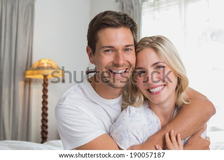 Portrait of a loving young man embracing woman from behind at home